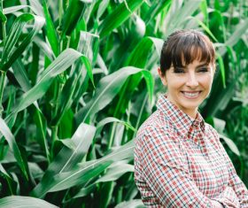 Smiling woman standing in corn field Stock Photo