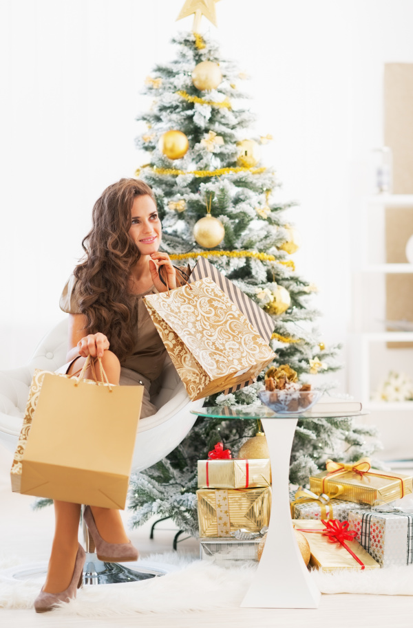 Smiling young woman with shopping bags near christmas tree 02