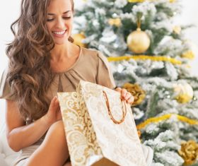 Smiling young woman with shopping bags near christmas tree 03