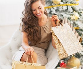 Smiling young woman with shopping bags near christmas tree 04