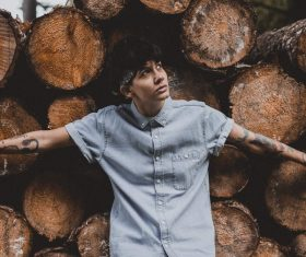 Stylish young man posing near wood logs Stock Photo