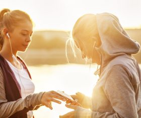 Two girls using smartphones listening to music Stock Photo 03