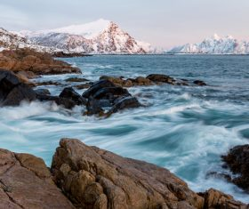 Wave splashing on frozen rocky beach Stock Photo