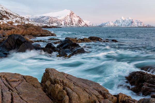 Wave splashing on frozen rocky beach Stock Photo