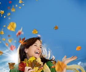 Woman collecting autumn leaves happy Stock Photo