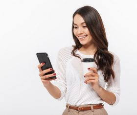 Woman holding coffee looks at mobile phone information Stock Photo