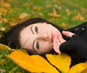 Woman lying on dead leaves Stock Photo