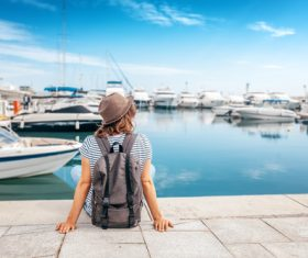 Woman sitting on pier watching yacht Stock Photo