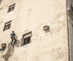 Worker climbing on building wall with rope Stock Photo