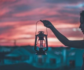 Young girl holding classical lamp at dusk Stock Photo