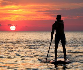 Young man rowing on calm sea at dusk Stock Photo