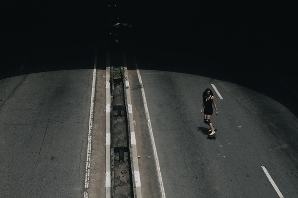 Young woman playing roller skate on road Stock Photo