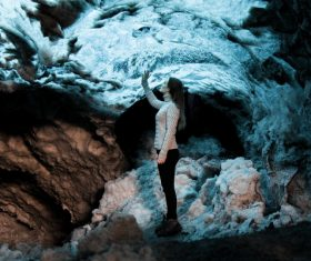 Young woman posing in frozen stone cave Stock Photo