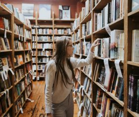 girl looking for books in library Stock Photo