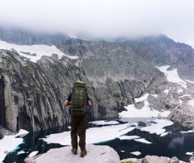 man exploring snowy mountain backpack Stock Photo