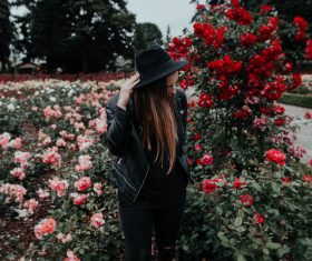 woman posing on beautiful blooming roses garden Stock Photo