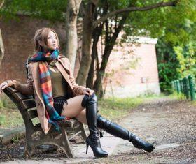 Asian girl posing on bench outdoors Stock Photo