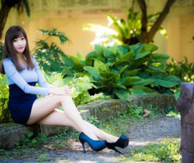 Asian pretty girl sitting on flower bed posing Stock Photo
