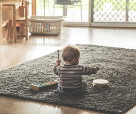 Baby playing alone on the carpet Stock Photo