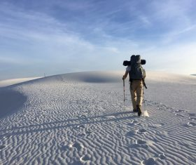 Backpacker hiking through the desert Stock Photo