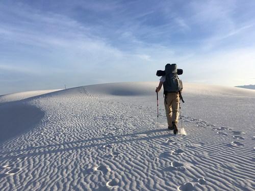 Backpacker hiking through the desert Stock Photo