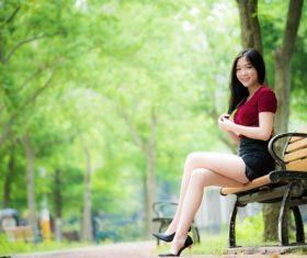 Beautiful Asian girl sitting on bench Stock Photo