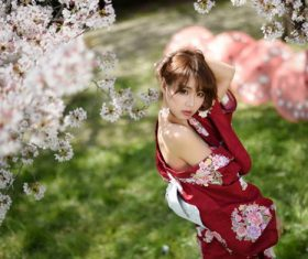 Beautiful Japanese girl under cherry blossom tree Stock Photo