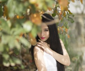 Beautiful asian girl posing under the plant Stock Photo