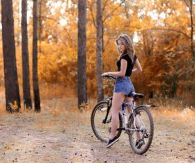 Beautiful girl riding bicycle looks back Stock Photo