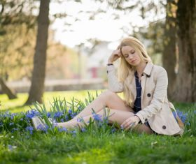 Beautiful girl sitting on the grass in the park Stock Photo