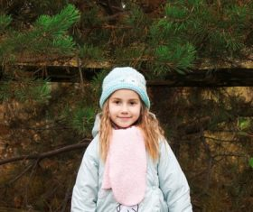 Beautiful little girl in front of pine trees Stock Photo