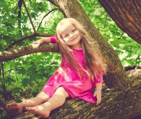 Blond little girl on big tree Stock Photo