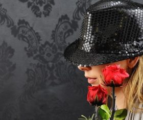 Blonde woman posing with black hat and roses Stock Photo