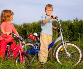 Brother and sister riding bicycle Stock Photo