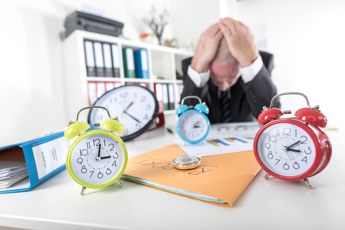 Clock on the desk and exhausted man Stock Photo