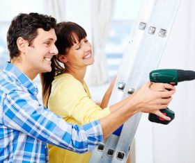 Couples with punch holes in the wall Stock Photo
