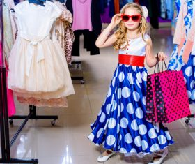 Cute little girl holding shopping bags posing in mall Stock Photo