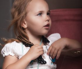 Cute little girl wearing a necklace Stock Photo