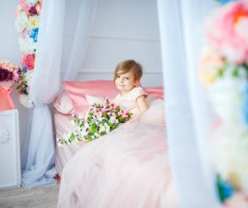 Dressed up beautiful little girl holding bouquet sitting on bed Stock Photo 01