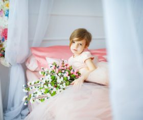 Dressed up beautiful little girl holding bouquet sitting on bed Stock Photo 02