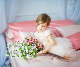 Dressed up beautiful little girl holding bouquet sitting on bed Stock Photo 03