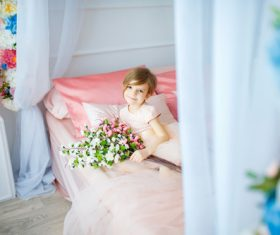 Dressed up beautiful little girl holding bouquet sitting on bed Stock Photo 04