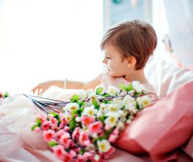 Dressed up beautiful little girl holding bouquet sitting on bed Stock Photo 05