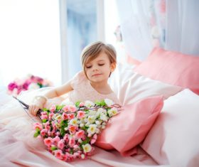 Dressed up beautiful little girl holding bouquet sitting on bed Stock Photo 06