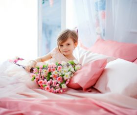 Dressed up beautiful little girl holding bouquet sitting on bed Stock Photo 07
