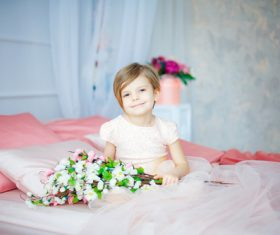 Dressed up beautiful little girl sitting on the bed Stock Photo 01