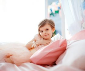Dressed up beautiful little girl sitting on the bed Stock Photo 02