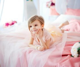 Dressed up beautiful little girl sitting on the bed Stock Photo 03