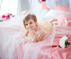 Dressed up beautiful little girl sitting on the bed Stock Photo 04