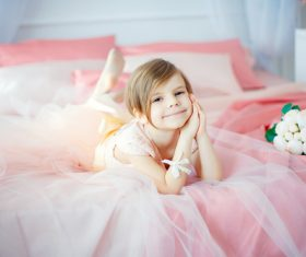 Dressed up beautiful little girl sitting on the bed Stock Photo 05